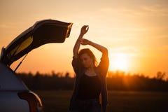 Mooie jonge vrouw die gelukkig en in de boomstam van een auto tijdens een wegreis dansen in Europa in de laatste notulen van Goud stock fotografie