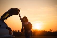 Mooie jonge vrouw die gelukkig en in de boomstam van een auto tijdens een wegreis dansen in Europa in de laatste notulen van Goud royalty-vrije stock afbeeldingen
