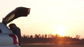 Mooie jonge vrouw die gelukkig en in de boomstam van een auto tijdens een wegreis dansen in Europa in de laatste notulen van Goud stock video