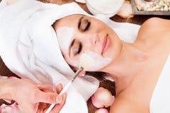 Mooie jonge vrouw die gezichtsmasker krijgt stock fotografie