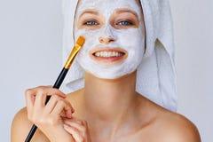 Mooie jonge vrouw die gezichtsmasker op haar gezicht met borstel toepassen Huidzorg en behandeling, kuuroord, natuurlijke schoonh stock foto's