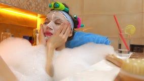 Mooie jonge vrouw die gezichtsmasker in schuimend bad toepassen Schoonheidsbehandelingen thuis 4k schot stock video