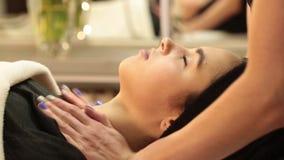 Mooie jonge vrouw die gezichtsmassage met gesloten ogen in een kuuroordsalon ontvangen stock video