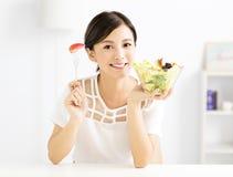 Mooie jonge vrouw die gezond voedsel eten Stock Afbeelding