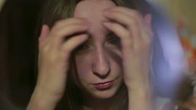 Mooie jonge vrouw die haar gezicht controleren stock videobeelden