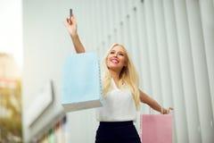 Mooie jonge vrouw die haar het winkelen zakken hoog houden omhoog Stock Afbeeldingen