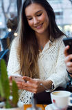 Mooie jonge vrouw die haar mobiele telefoon met behulp van bij koffiewinkel Stock Afbeelding