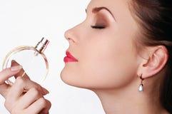 Mooie jonge vrouw die haar parfum ruikt stock afbeelding