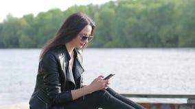 Mooie jonge vrouw die haar telefoon met behulp van stock video