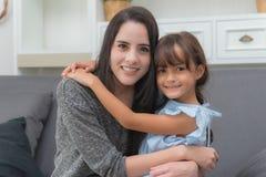 Mooie jonge vrouw die haar zuster op bank in het leven r koesteren Royalty-vrije Stock Foto's