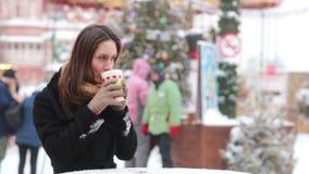 Mooie jonge vrouw die hete thee drinken tijdens de Kerstmismarkt stock footage