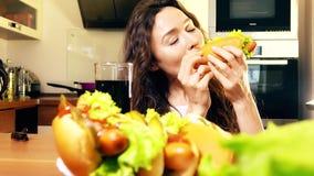 Mooie jonge vrouw die hotdog thuis eten en kola drinken stock footage