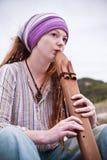 Mooie jonge vrouw die houten fluit speelt Stock Afbeelding