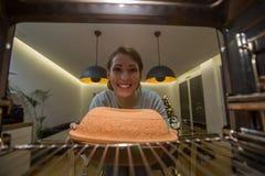 Mooie jonge vrouw die iets in de oven voorleggen aan kok stock foto's