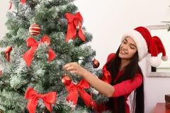 Mooie jonge vrouw die in Kerstmanhoed Kerstmis verfraaien stock foto's