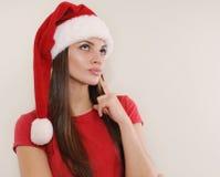 Mooie jonge vrouw die in Kerstmanhoed over Kerstmisgift denken stock fotografie