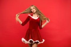 Mooie jonge vrouw die in Kerstmankostuum met een bundel die van haar lang zijdeachtig haar spelen, camera op rode achtergrond bek Stock Fotografie