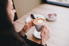 Mooie jonge vrouw die koffie van cappuccino met schuim genieten dichtbij venster Stock Foto