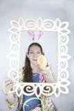 Mooie jonge vrouw die konijnoren dragen en geel lovertjepaasei houden Royalty-vrije Stock Afbeeldingen