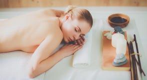 Mooie jonge vrouw die kuuroordmassage krijgen, die op salon liggen Stock Fotografie