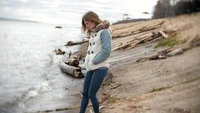 Mooie jonge vrouw die langs de rivierbank lopen en droge takken verzamelen stock videobeelden