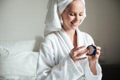 Mooie jonge vrouw die lichaamslotion na een douche toepassen stock foto's
