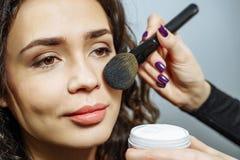 Mooie jonge vrouw die make-up met een borstel toepassen tegen een grijze achtergrond royalty-vrije stock afbeelding