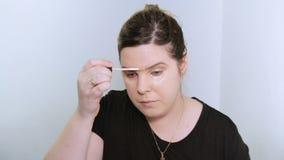Mooie jonge vrouw die make-up toepast stock footage