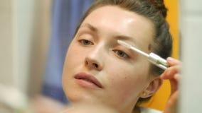 Mooie jonge vrouw die mascara en make-up voor spiegel in badkamers in de ochtend zetten stock video