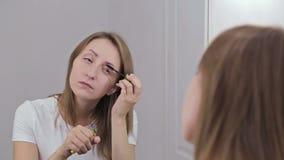 Mooie jonge vrouw die mascara voor spiegel zetten stock videobeelden