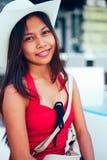 Mooie jonge vrouw die met de hoed op de strandtoevlucht glimlachen, de zomervakantie Stock Afbeelding