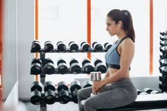 Mooie jonge vrouw die met domoor in de gymnastiek uitoefent Stock Afbeelding
