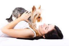Mooie jonge vrouw, die met een leuk hondras Yorkshire liggen Terrier Royalty-vrije Stock Foto's