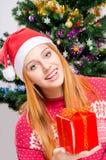 Mooie jonge vrouw die met Kerstmanhoed aanbiedend u aanwezige Kerstmis glimlachen. Royalty-vrije Stock Afbeeldingen