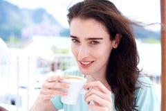 Mooie jonge vrouw die met koffiekop glimlachen royalty-vrije stock afbeelding