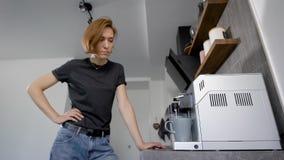 Mooie jonge vrouw die met kort haar hete koffie in koffiemachine maken stock videobeelden