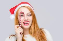 Mooie jonge vrouw die met santahoed houdend een suikergoedriet voor het oog glimlachen. Royalty-vrije Stock Foto