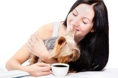 Mooie jonge vrouw die met Yorkshire Terrier ochtendkoffie drinken Royalty-vrije Stock Afbeeldingen