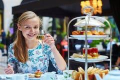 Mooie jonge vrouw die middag van thee genieten royalty-vrije stock afbeelding