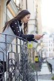Mooie jonge vrouw die mobiele telefoon in openlucht met behulp van in Royalty-vrije Stock Foto's