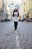 Mooie jonge vrouw die mobiele telefoon in openlucht met behulp van in Royalty-vrije Stock Foto