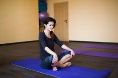 Mooie jonge vrouw die na het doen van yogaoefeningen, zittend mediteren, die met gesloten ogen rusten ontspannen Royalty-vrije Stock Foto's
