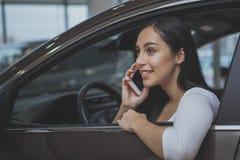 Mooie jonge vrouw die nieuwe auto kopen stock foto