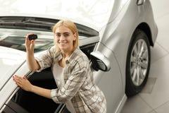 Mooie jonge vrouw die nieuwe auto kopen bij het handel drijven stock foto