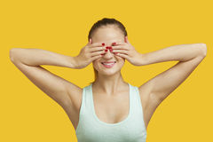 Mooie jonge vrouw die ogen over gele achtergrond behandelen Royalty-vrije Stock Fotografie