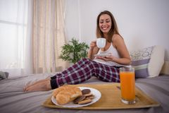 Mooie jonge vrouw die ontbijt in bed hebben stock foto's
