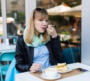 Mooie jonge vrouw die ontbijt eet stock fotografie