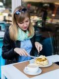 Mooie jonge vrouw die ontbijt eet stock afbeelding