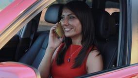 Mooie jonge vrouw die op de telefoon en de glimlach in haar auto spreken stock footage