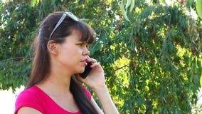 Mooie jonge vrouw die op de telefoon in park spreekt stock videobeelden